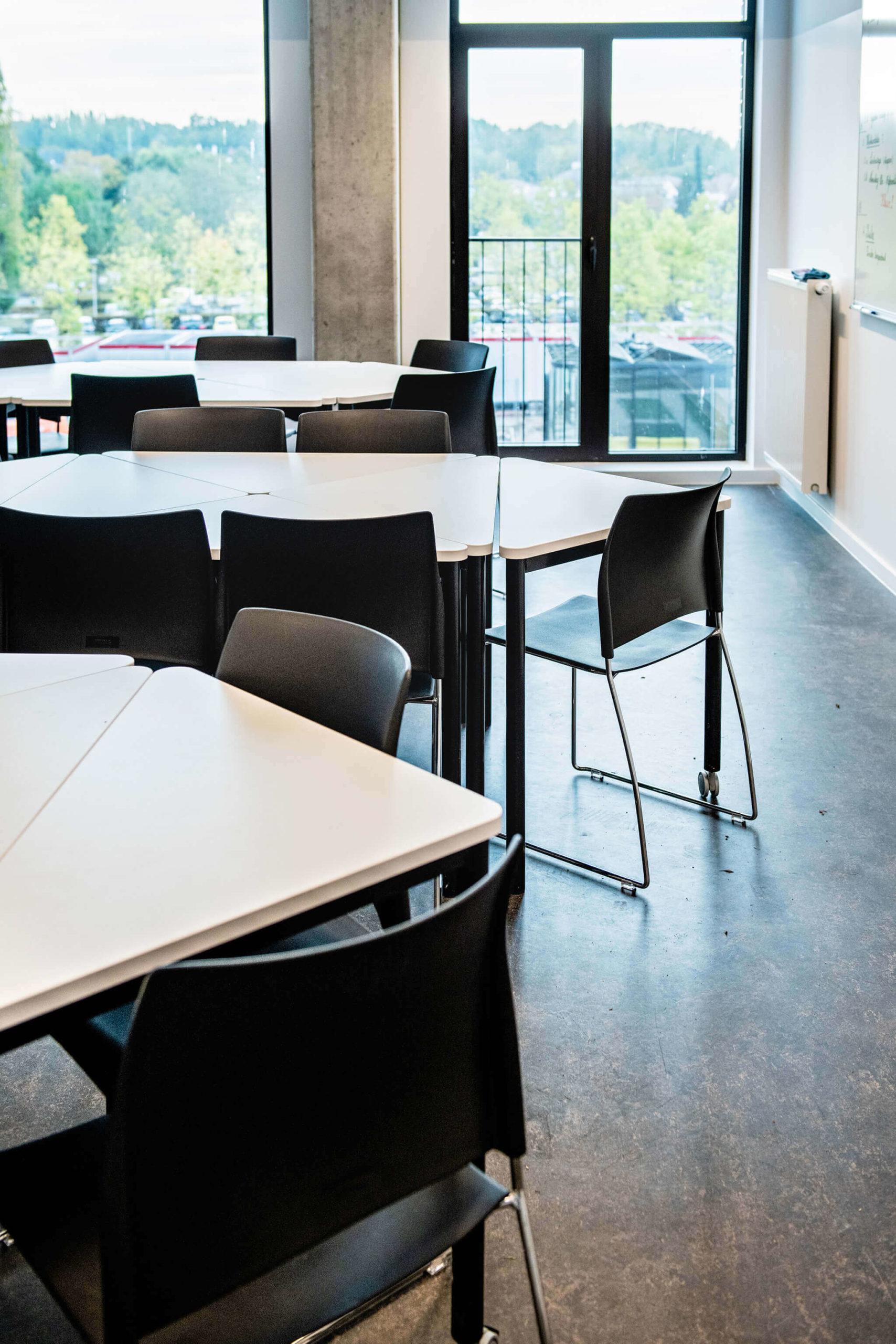 Leslokaal bij Vives Kortrijk met stapelbare stoelen en unieke mobiele driehoekige tafels.