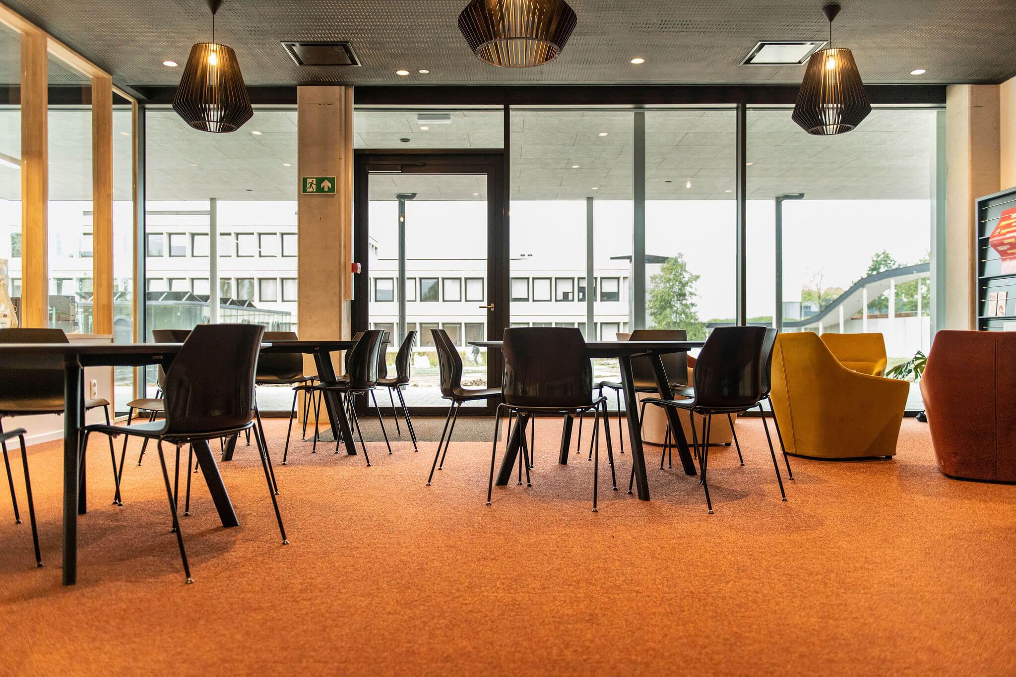 Lerarenkamer Vives Kortrijk met tafels en zwarte Kalea stoelen, vergezeld van een zithoek met Chic fauteuils